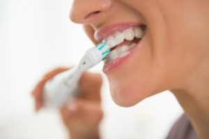 a woman using an electric toothbrush to brush her teeth at home