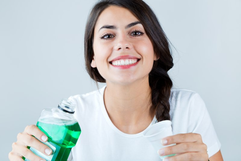 a young woman preparing to pour mouthwash into a cup to perform a rinse