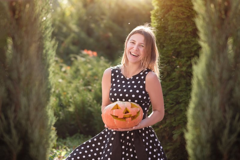 a woman standing outside and holding a carved Halloween pumpkin