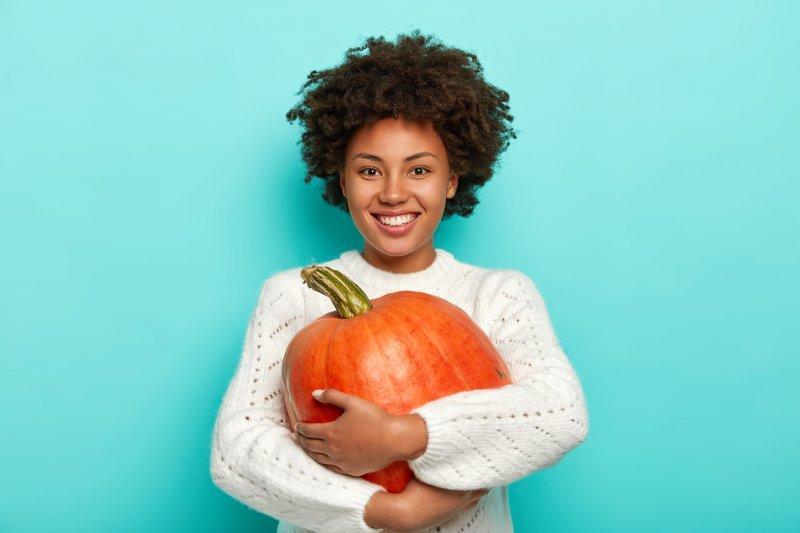 a young woman wearing a white sweater, holding a pumpkin, and smiling