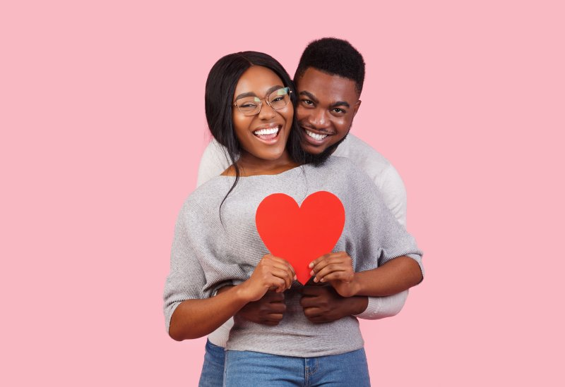 a young man and woman hugging and holding a red heart for Valentine's Day