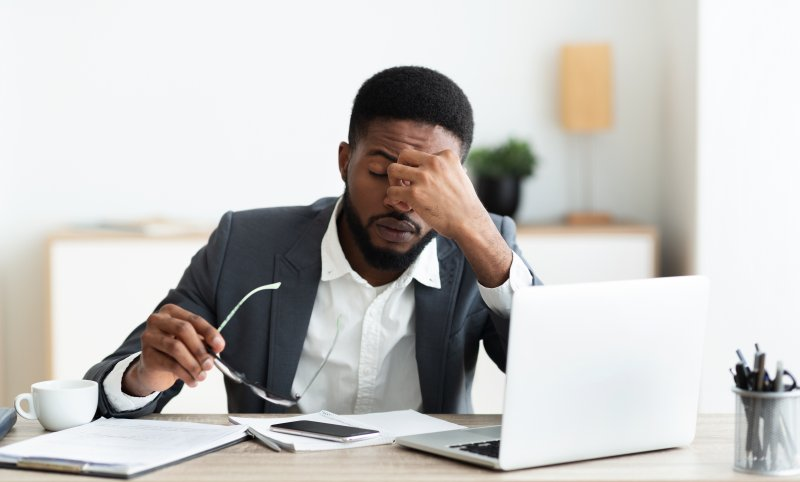 a young man working behind his computer and feeling stressed