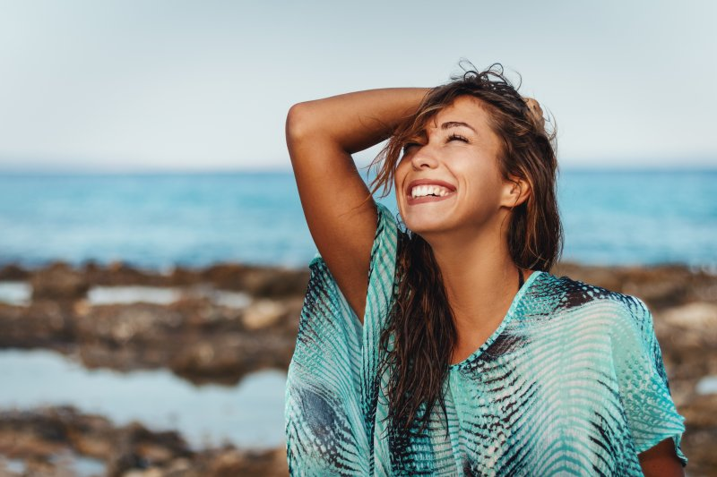 a young woman standing on the beach and smiling